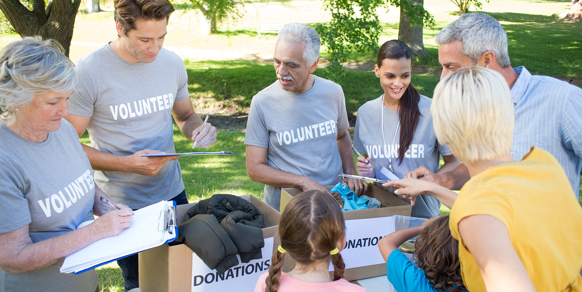 """A group of diverse volunteers gathered around several boxes labeled """"Donations"""""""